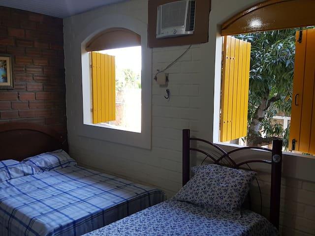 Quarto com suíte, chuveiro elétrico, 1 cama de casal, 2 de solteiros, ar-condicionado e guarda-rouoa.