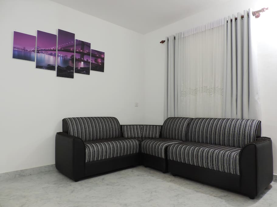 200sqft sitting area comprising of a modern sofa, dining table with 6 chairs etc.