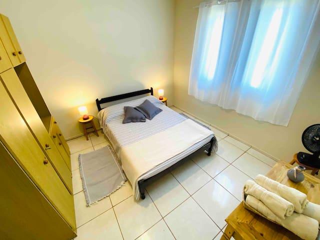 Quarto 2 com cama de casal, ventilador, guarda-roupa e janela de frente para o mar.