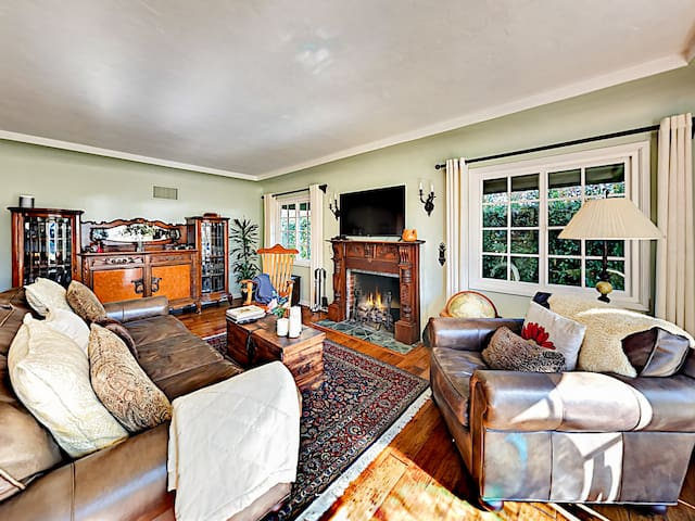 A hand carved wood fireplace anchors the sunlit living room that offers a sofa and 2 armchairs.