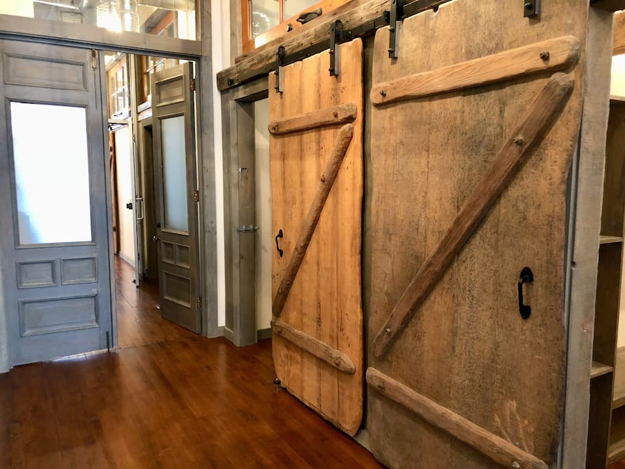 The 9 foot tall dual entry doors are the original main entry doors to the building that have been saved and repurposed.  Dual sliding barn doors were custom made of aged white oak by a local artisan wood worker.