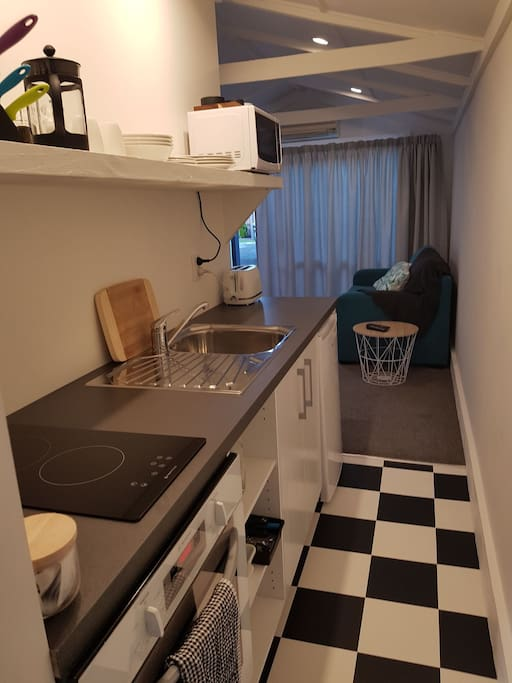 Modern galley kitchen includes Westinghouse oven, two electric hobs, under bench fridge and microwave.