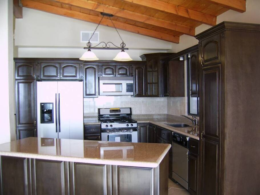 Full kitchen with stainless steel appliances.
