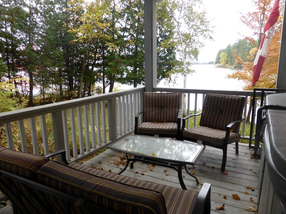 Deck outside living room close to the lake, with patio furniture.