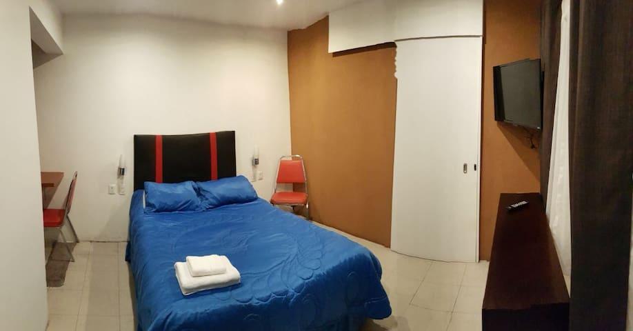 Bed and flat TV with local HD channels/Se ve la cama y una televisión plana con canales locales en HD