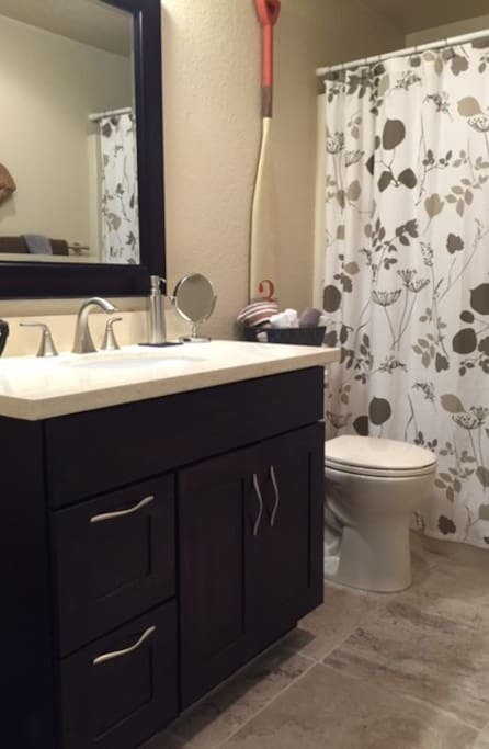 Recently remodeled bathroom with tub/shower, heated tile floors and marble countertops.