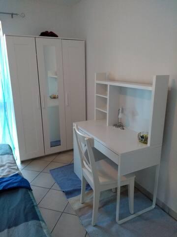 Schlafzimmer mit Schreibtisch und Schrank für Kleidung und Koffer (bedroom with desk and wardrobe with storage for clothing and suitcase)