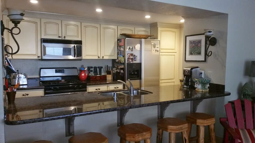 Updated kitchen with granite counter and 5 bar stools
