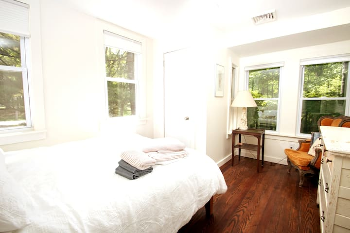 Our queen bedroom is quiet + quaint - welcoming you to cozy up for a nap or a good night's sleep.