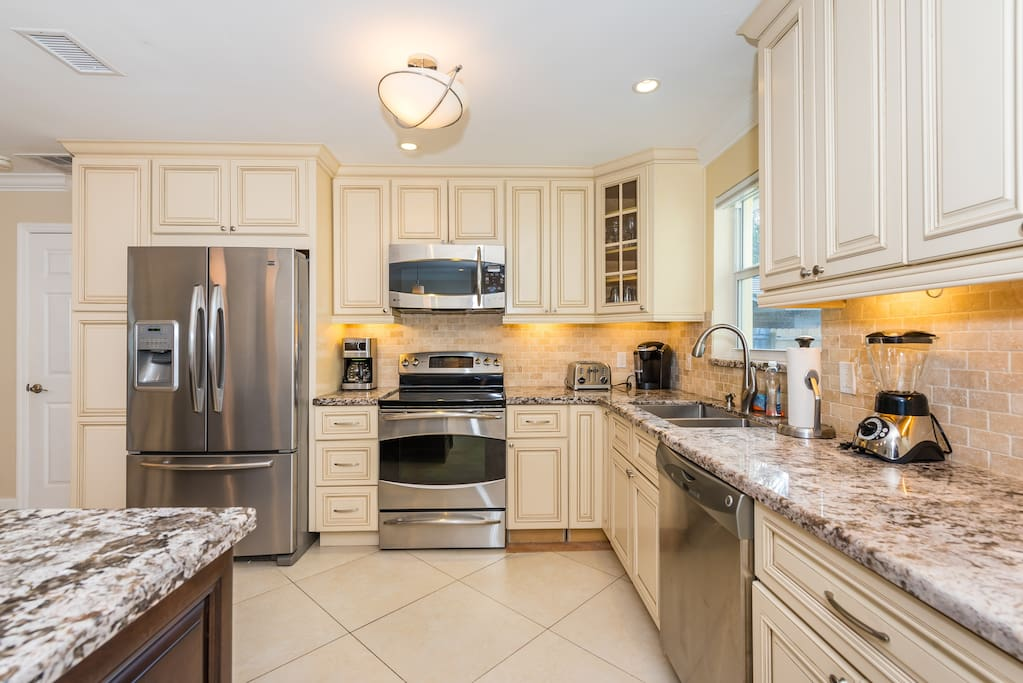 Marble countertops and high-end stainless steel appliances shine in the well-equipped kitchen.