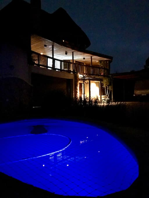 Pool at night with house