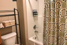 Tub, shower and toilet in private room.