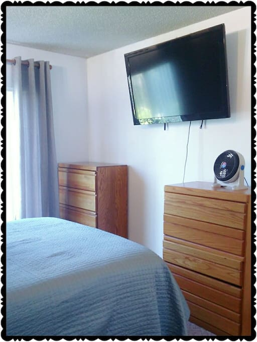 Two Dressers, fan, TV with Apple TV, Curtains, and Queen Bed.