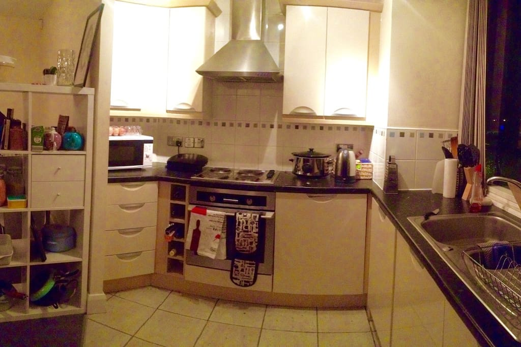 Kitchen with hobs, oven, microwave, slowcooker, grill and lots of pots and pans