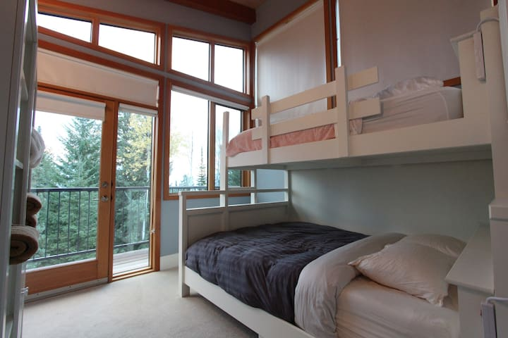 Third bedroom with single bunk beds and private balcony looking over the valley