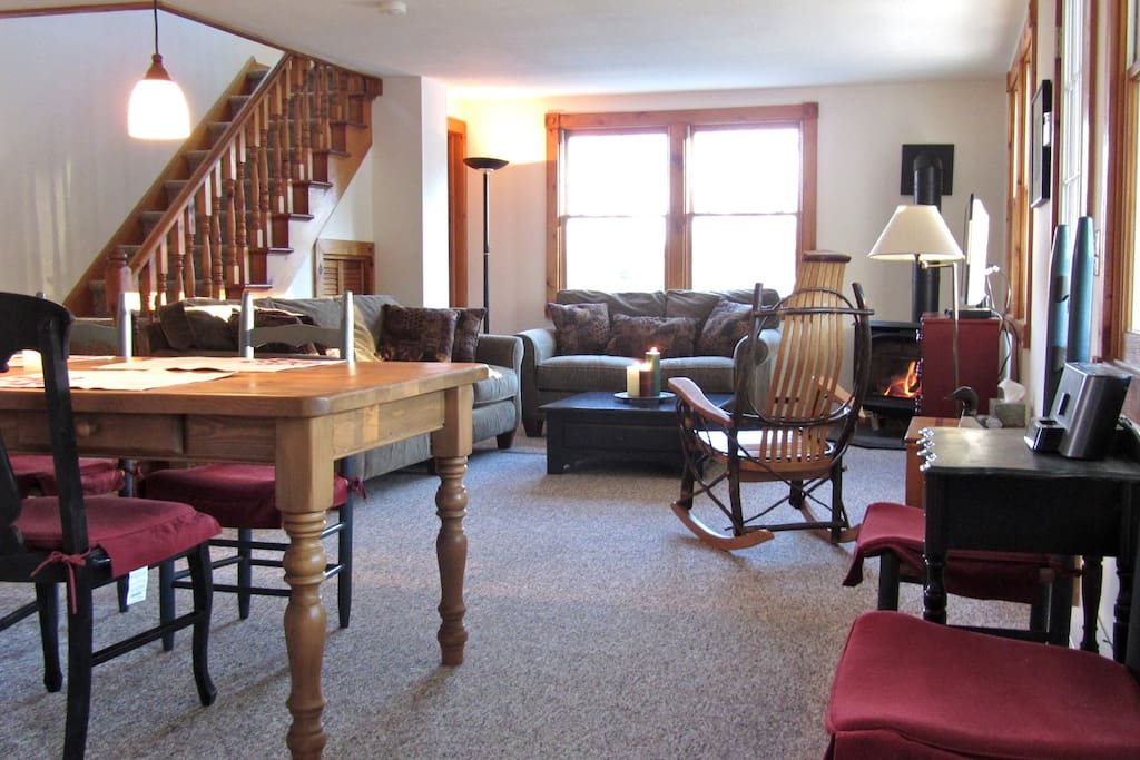 Living room with gas fueled wood-stove.  Staircase to King suite.
