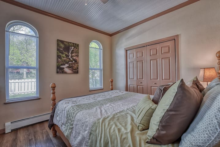 Bedroom has 2 arched front windows with front yard view.