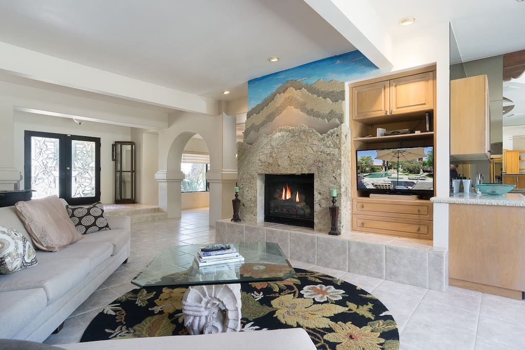 A sectional couch in the living room offers seating around the wood burning fireplace.