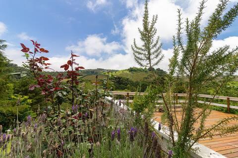 Jardim florido e deck com vista para a colina