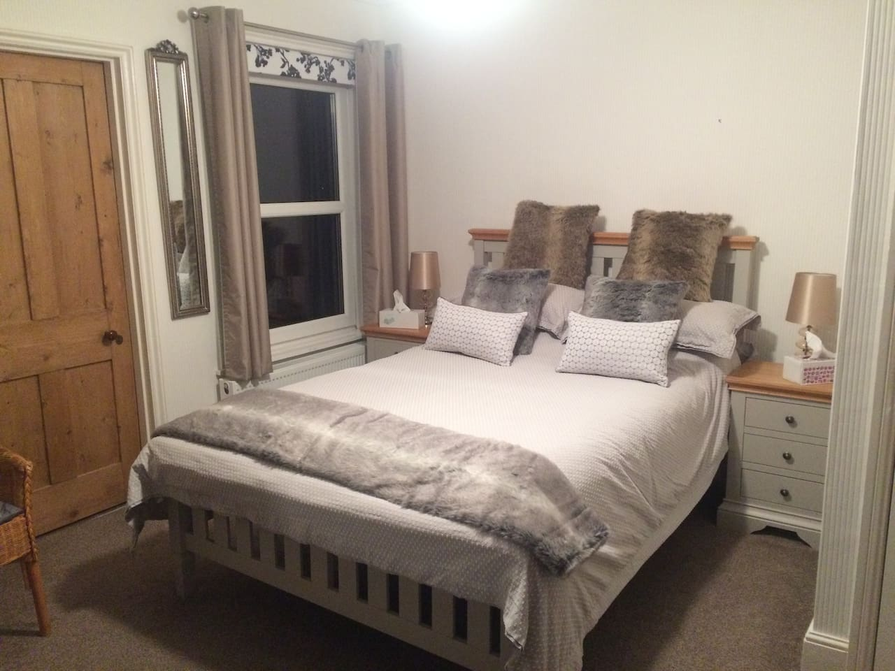 Comfortable guest bedroom with two three drawer side tables, wardrobe and large chest of drawers.