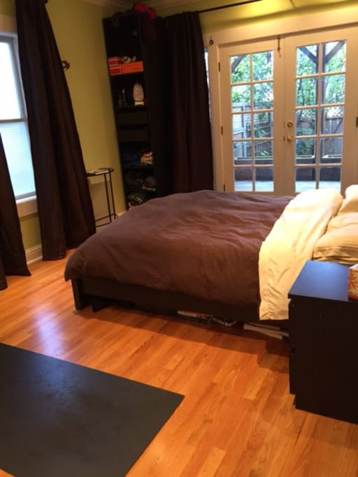 Master bedroom with ensuite bathroom and doors out to the back deck and the back yard.  Queen-sized mattress.