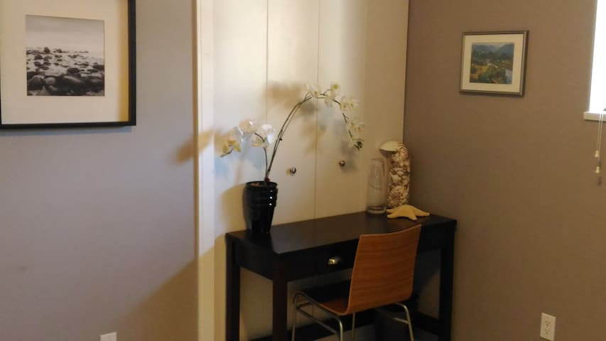 Writing desk and chair in room for your comfort , perfect for laptop.