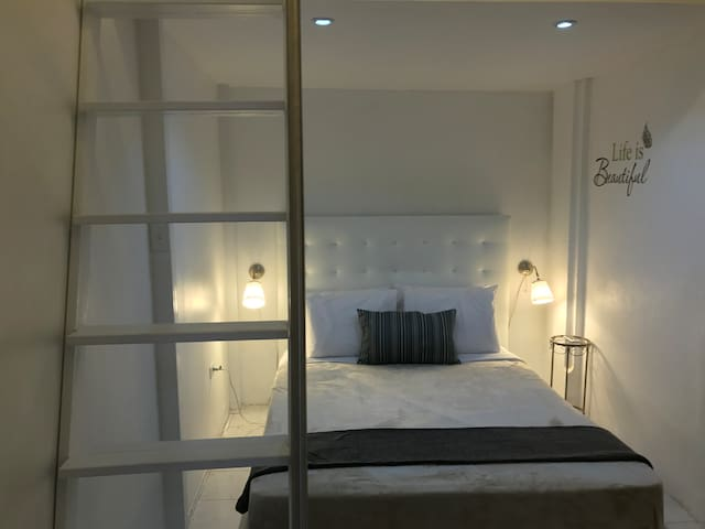 Vista al área del dormitorio. Tiene una cama tamaño Queen size, permitiendo acomodar fácilmente a dos personas; en adición a lo anterior, contamos con aire acondicionado en la habitación.