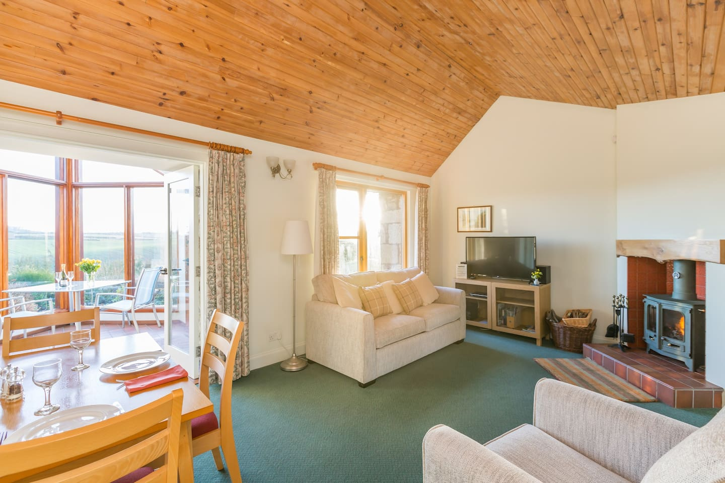 Begrum cottage living room has a wood burning stove, 3-seater sofa bed, another comfy chair, Smart TV with fibre Wi-Fi. There is dining area chairs & table for 4.