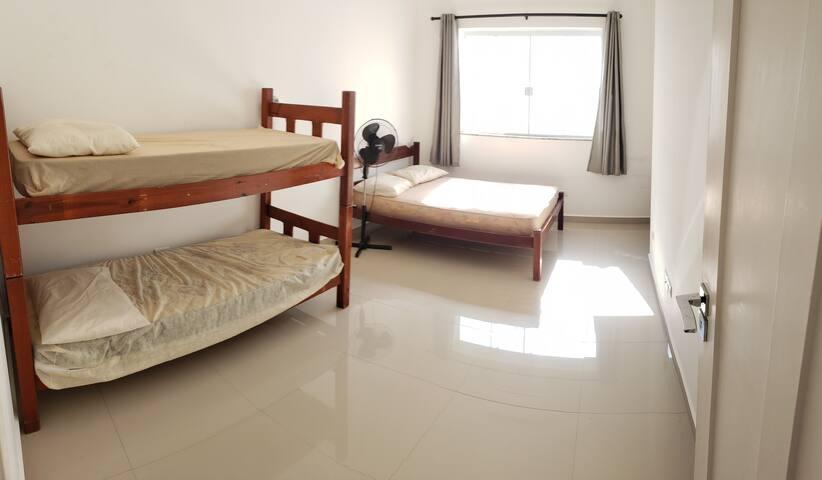 Quarto 3 - Conta com 1 beliche, 1 cama de casal e uma bancada de trabalho.