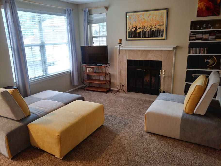 Spacious living area with lots of natural light and a wood burning fireplace.