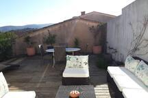 Terrasse ensoleillée, sans vis à vis direct. Equipée d'un transat, une table avec quatre chaises et un salon de jardin.