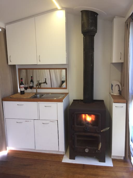Kitchen cupboards, roll out fridge, bin in drawer, electric kettle, wood fire with oven.