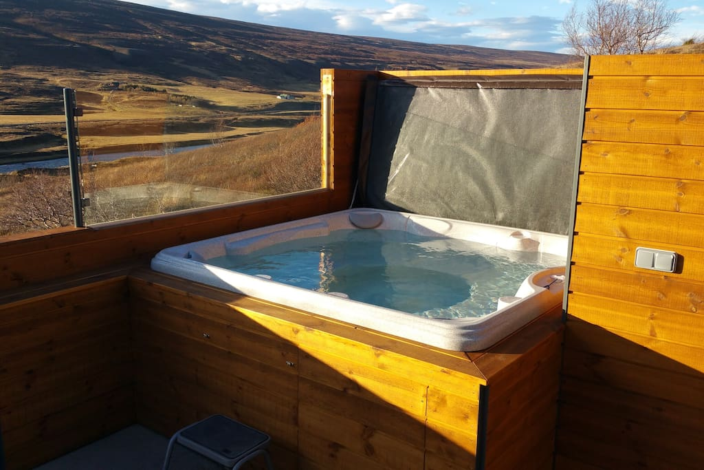Hot tub spa with an automatic heating system and a shower outside are accessible from upper bathroom