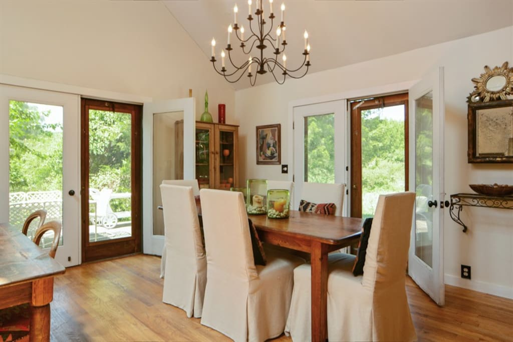 Dining area with antique farm table has  French doors to deck.