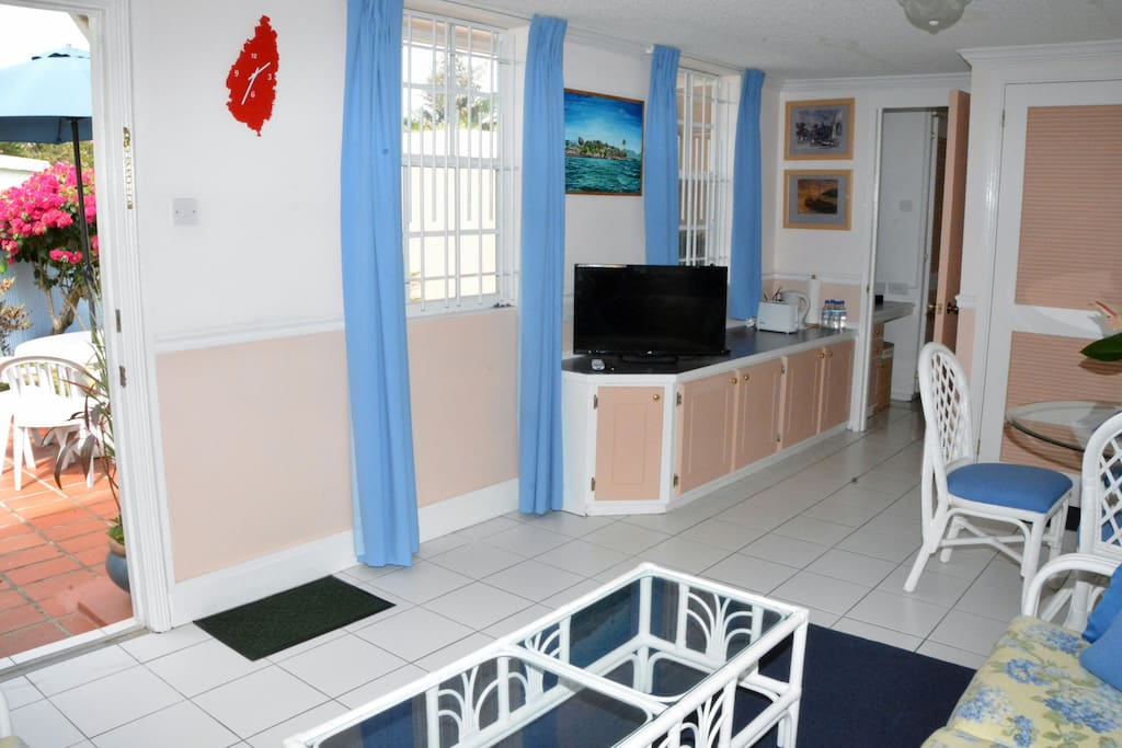 Living and dining space showing television and front door (open)