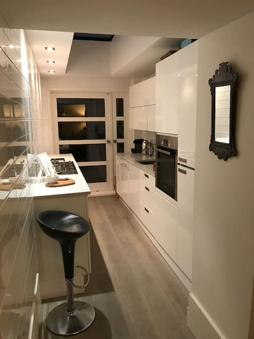 Open plan modern kitchen with Nespresso coffee maker, microwave, dishwasher and all standard appliances