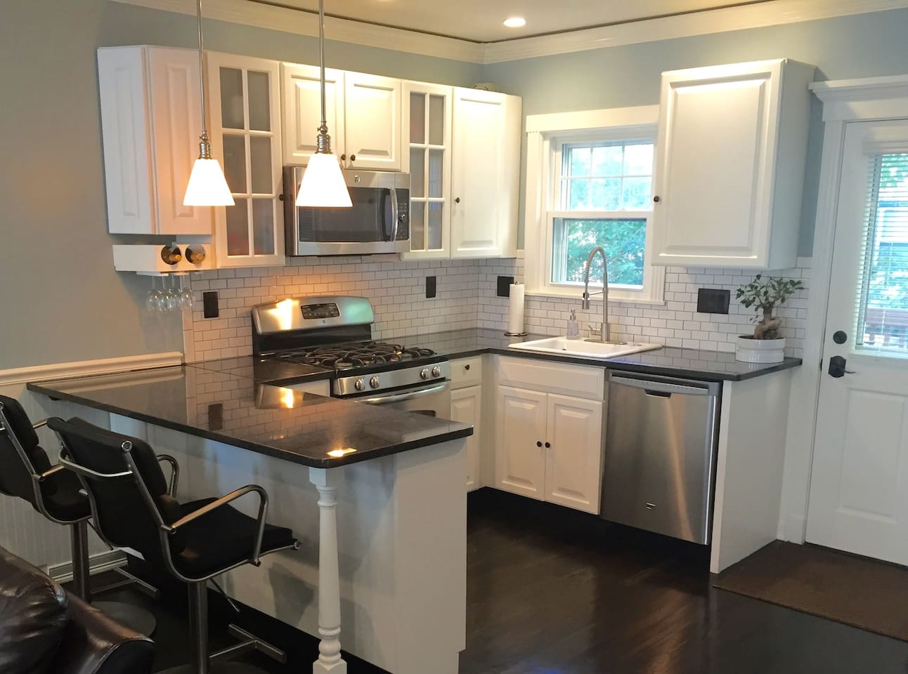 Chef's kitchen with dimmable lighting and direct access to full screen/glass door off of kitchen leading to attached deck and grill/seating area.