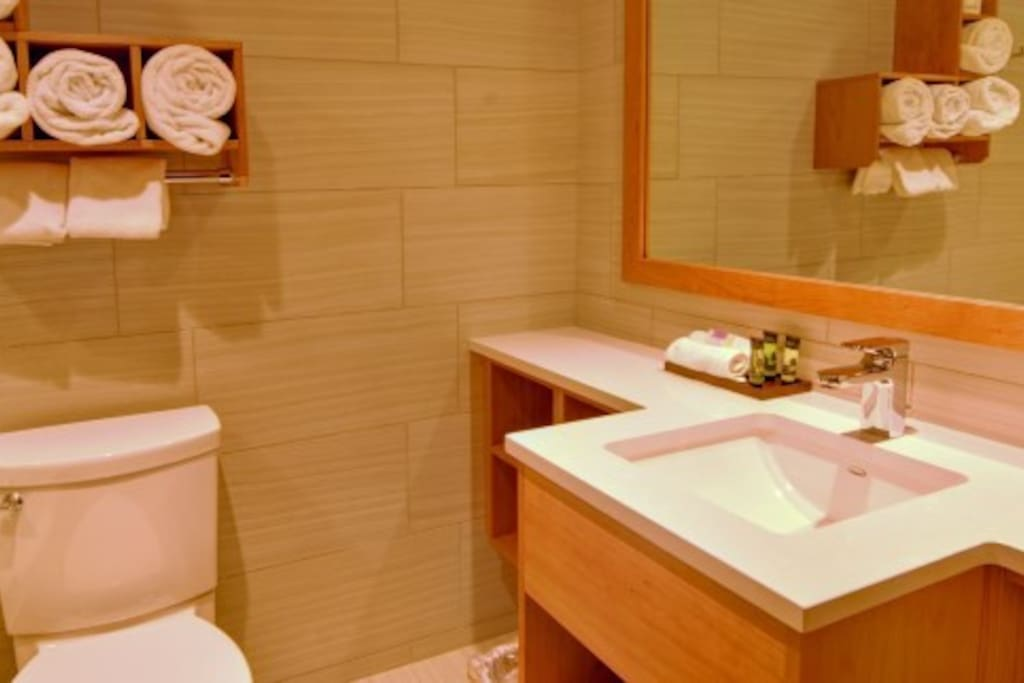 Prepare for your day outside in the spacious bathroom featuring warm wood touches.