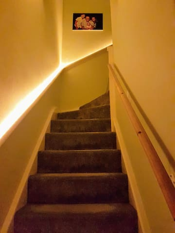 A warmly lit stairway that leads upstairs to rooms & bathroom.