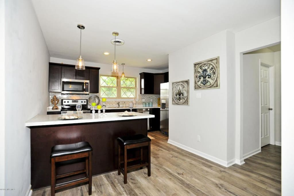 Beautiful modern open concept kitchen with full size appliances stove, microwave, dishwasher and refrigerator with filtered water. Coffee maker. Plus all dishes, silverware, pots and pans to cook a great meal.