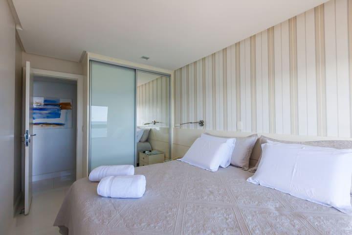 cama king com luminarias no teto e ao dois lados da cama