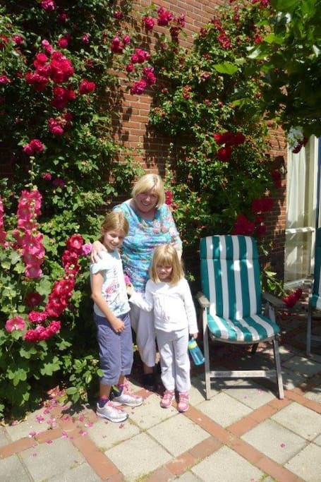 Beautiful roses and hollyhocks against the wall behind the house
