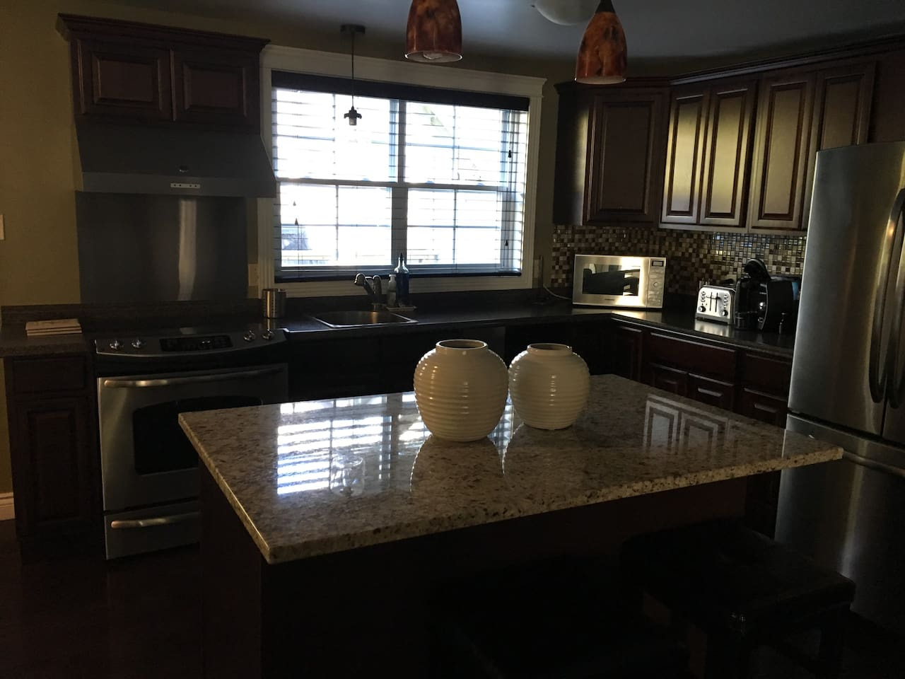 Bright sunny kitchen stainless appliances and granite island with two stools for seating.