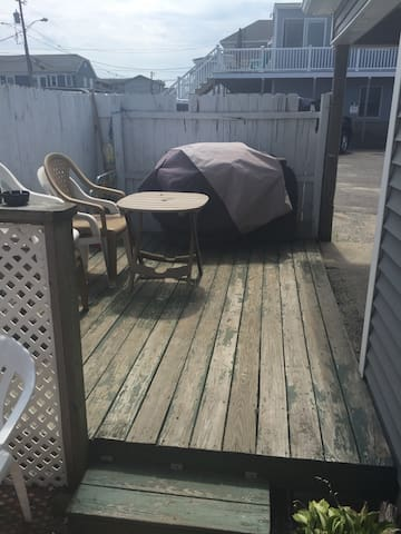 Small deck in the front of the house. A grill for BBQs and seating for enjoying the sea air.