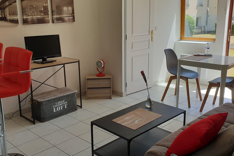 """Bienvenue chez """"nous""""  Pièce à vivre salon avec bar et cuisine aménagée, avec coin repas/bureau, table basse et TV, lave-linge...."""