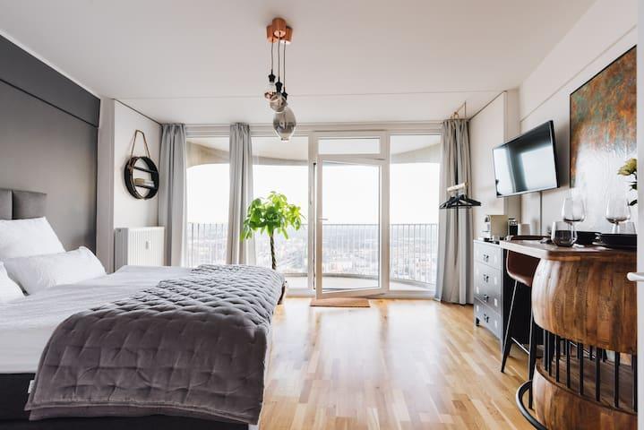Blick in den Raum mit Boxspringbett, stylischer Essecke und 40 Zoll Smart TV.