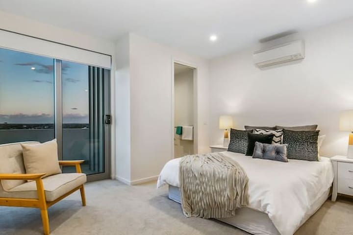 Master bedroom with a balcony overlooking the beach.