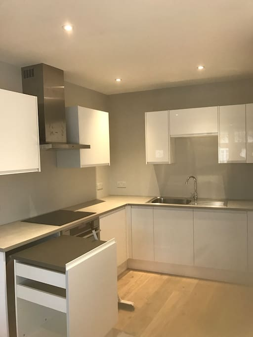 Modern Kitchen with Integrated Fridge, Freezer, Microwave, Oven, Four Burner Hob & Extractor Fan.