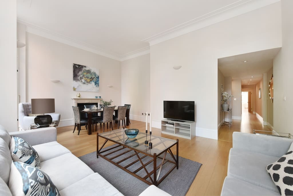 The spacious, bright and elegant Lounge and dining area with TV and balcony overlooking the gardens