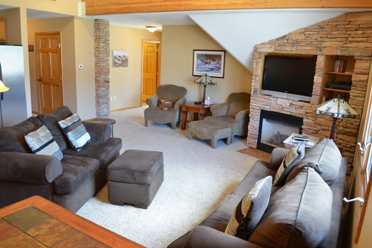 Living room is spacious and the rock fireplace provides a nice touch of warmth.